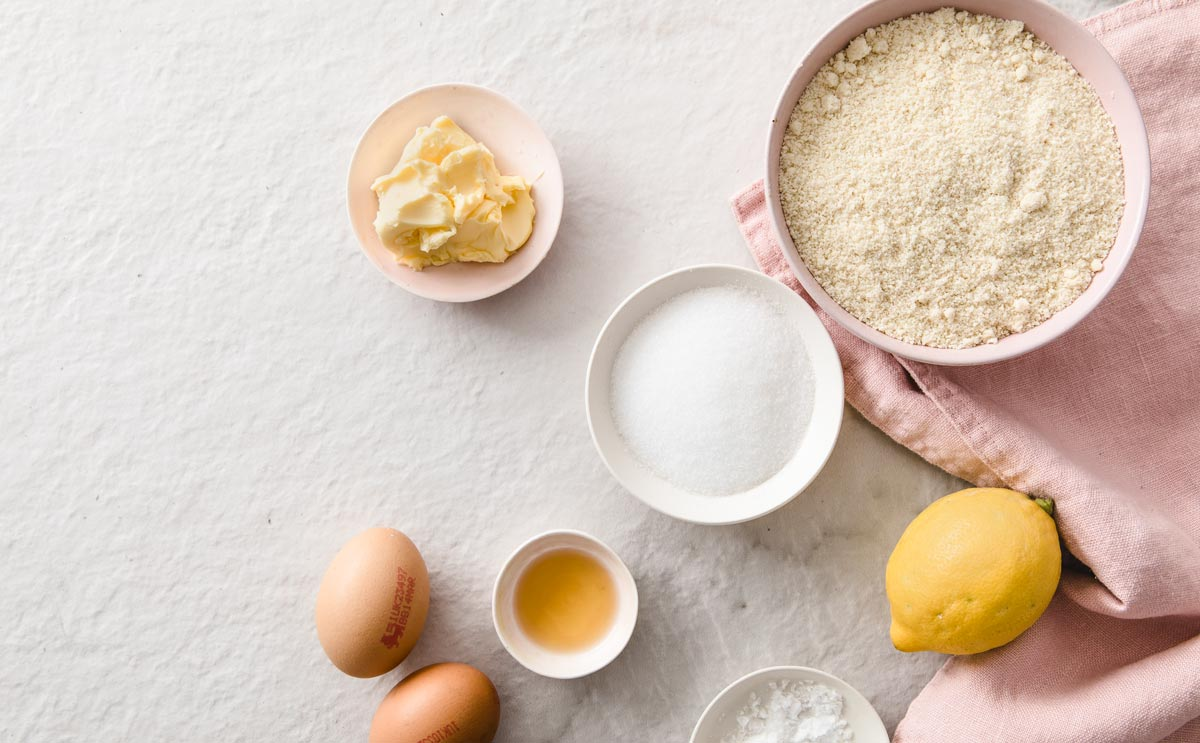 ingredients such as almond flour, erythritol, eggs, butter and lemon in bowls