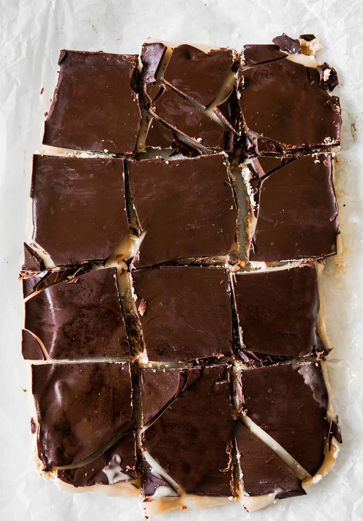 caramel slice squares topped with a chocolate layer on parchment paper