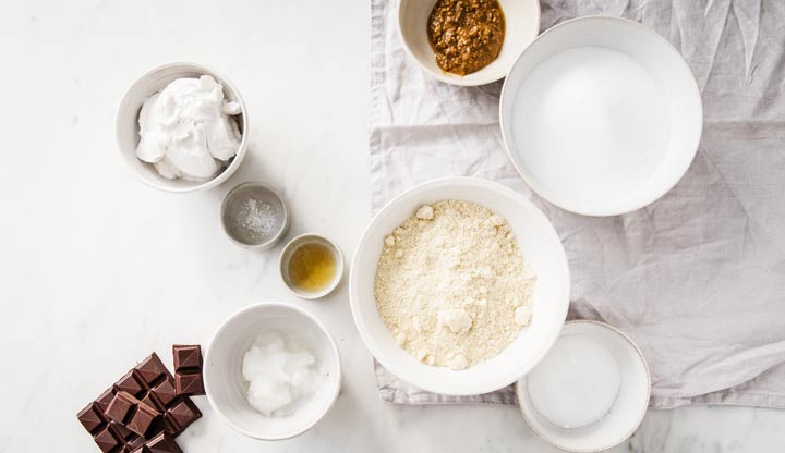Ingredients such as almond flour, chocolate, sweetener and coconut oil in bowls