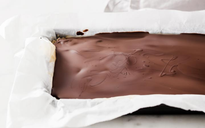 melted chocolate topping spread over caramel and almond flour base layer in a baking pan lined with parchment paper