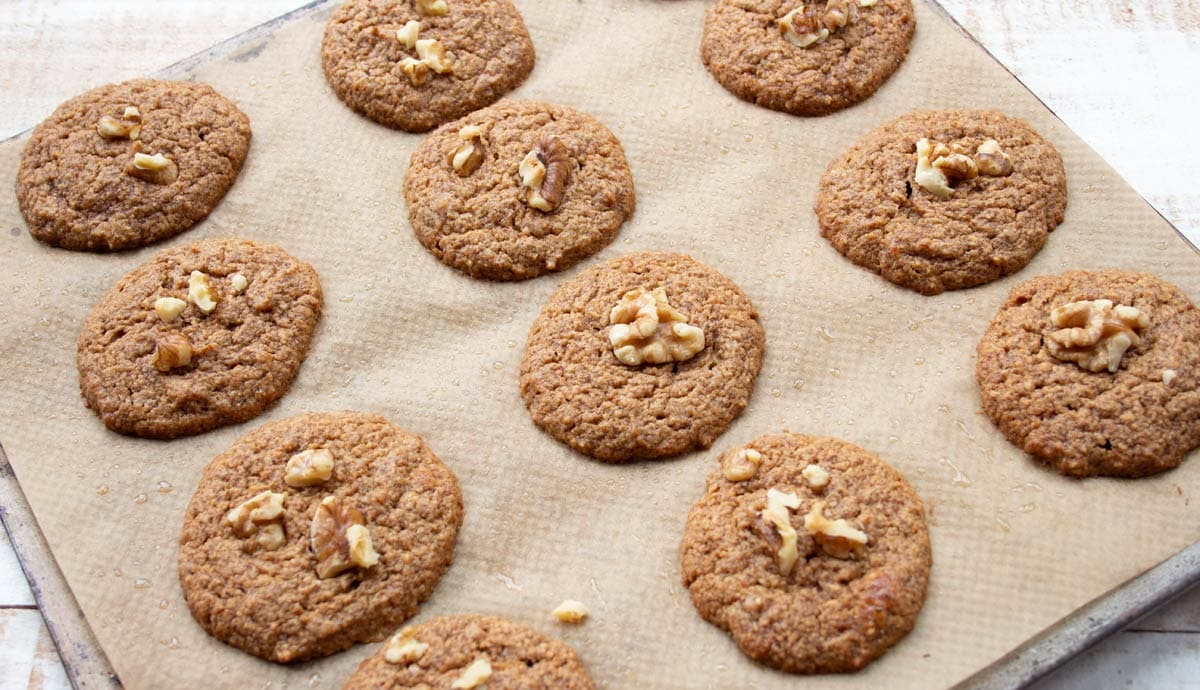 banana bread cookies topped with walnuts on a baking tray lined with parchment paper