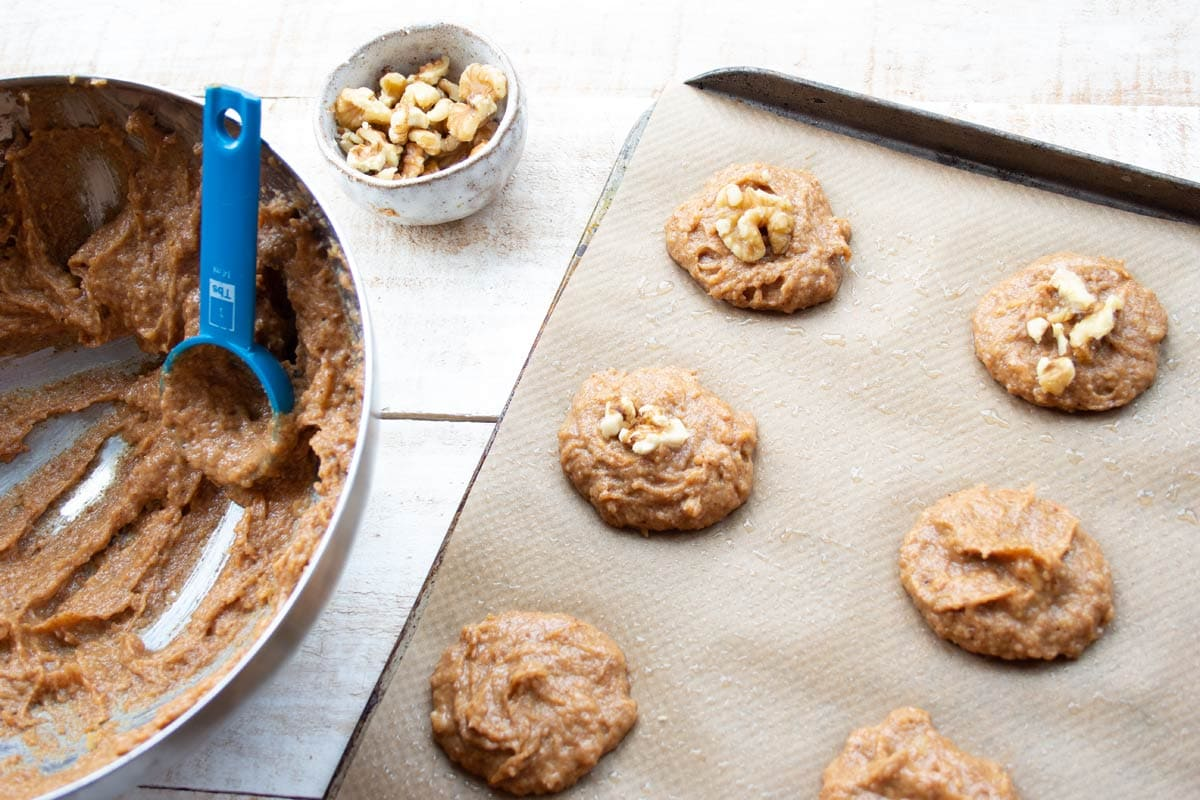 unbaked cookies on a tray and a bowl filled with batter and a measuring spoon