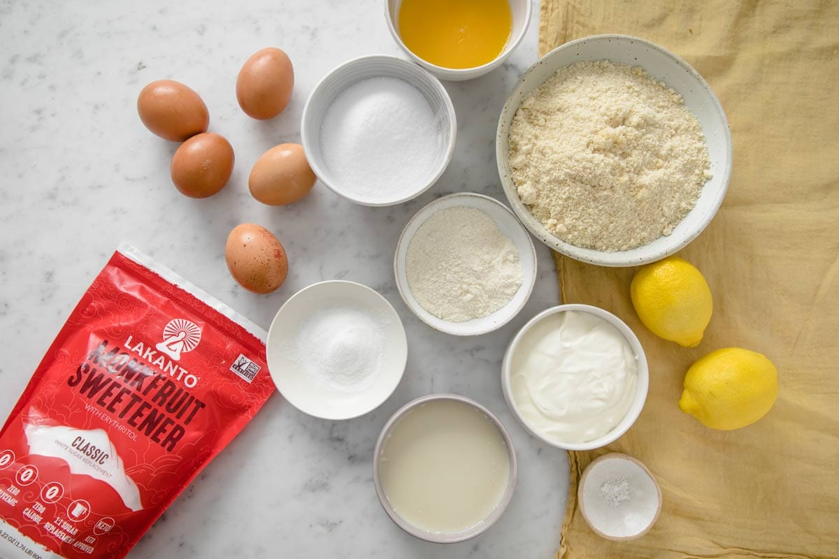 eggs, flours, lemons, sweetener and all other ingredients for lemon cake measured into bowls