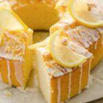 A round Keto lemon pound cake topped with a glaze and lemon slices and a cake piece cut out