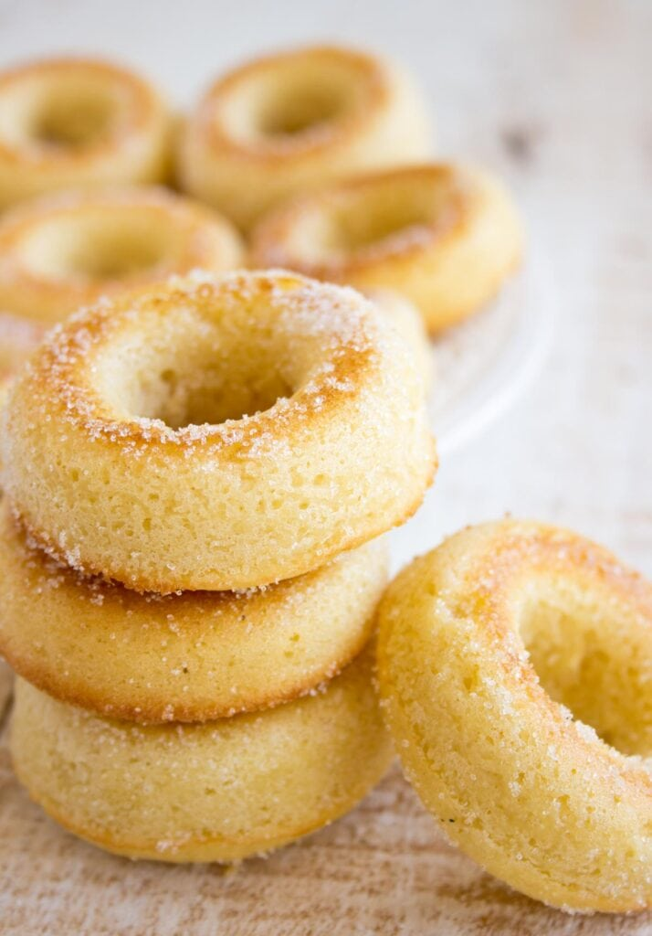 Three donuts coated in erythritol stacked on top of each other and another one leaning against the stack.