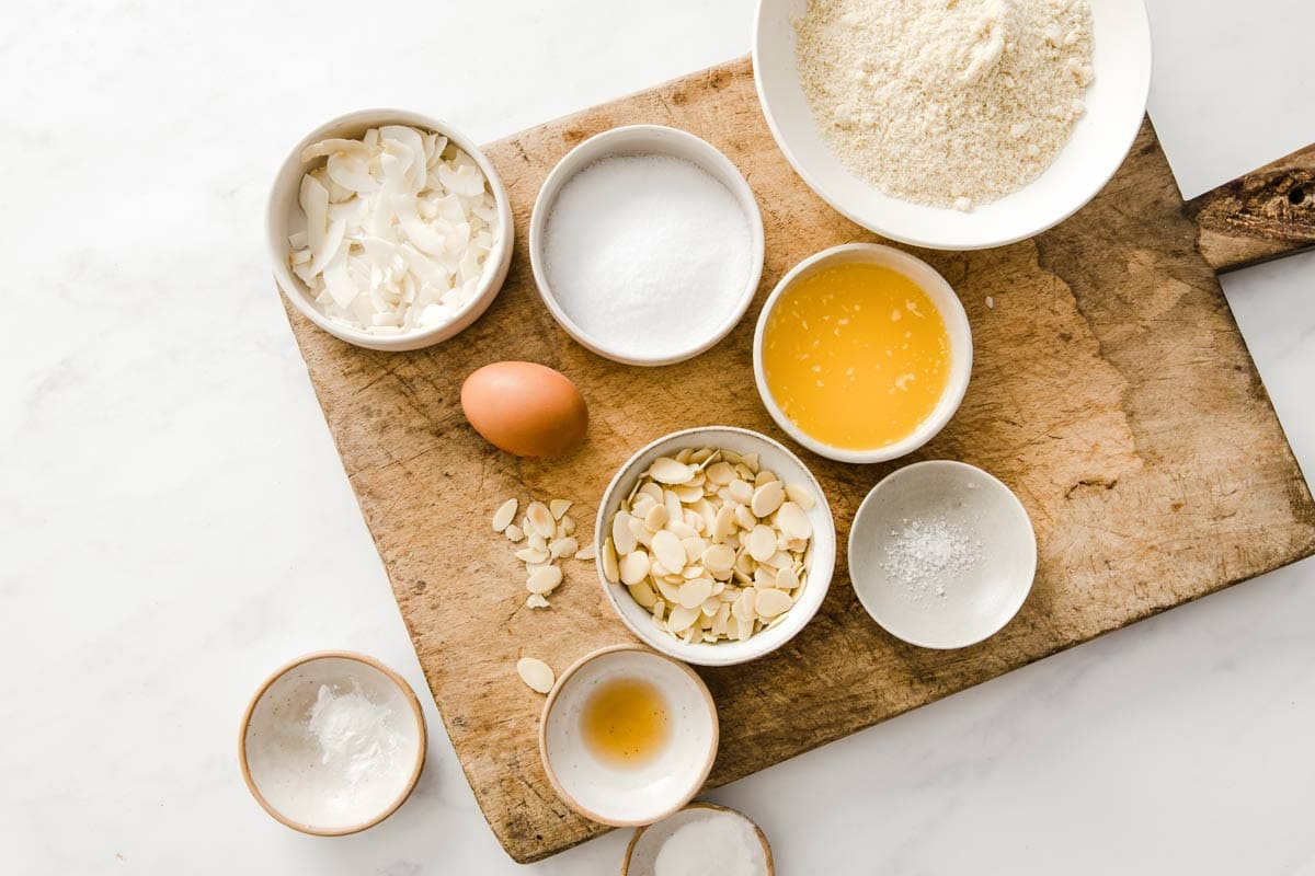 cookie ingredients such as butter, almond flour, almond flakes and coconut chips in bowls