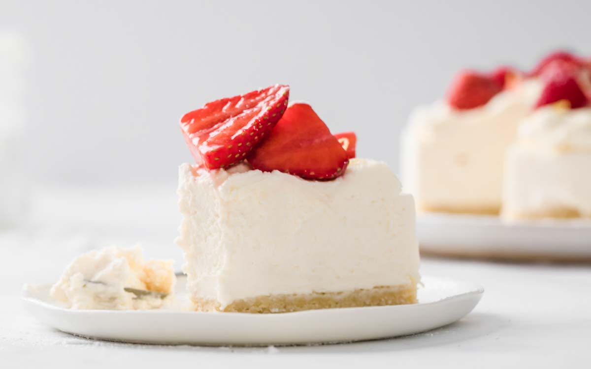 a slice of sugar free cheesecake topped with strawberries on a plate