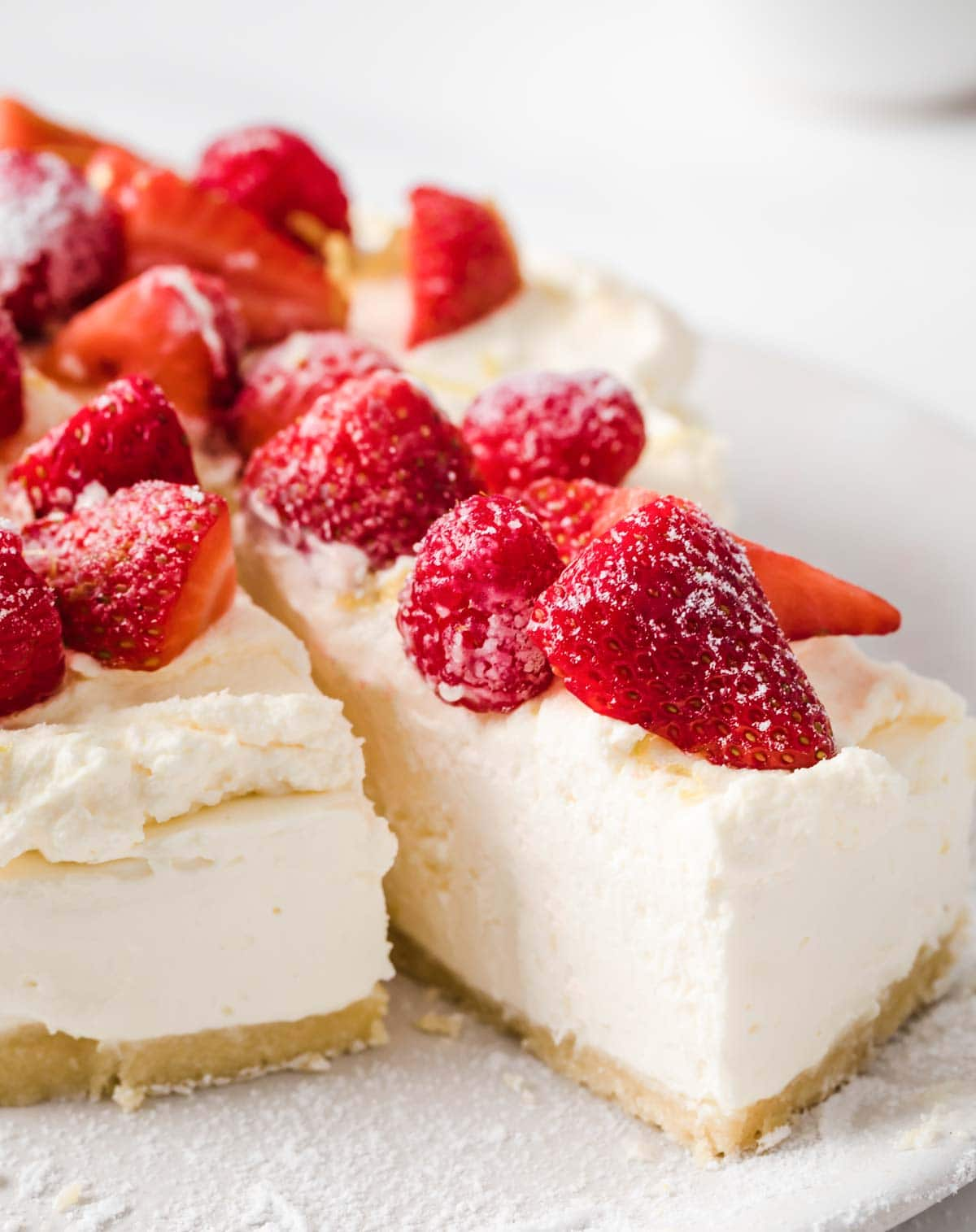 a slice of cake half removed from a sugar free cheesecake topped with strawberries and raspberries