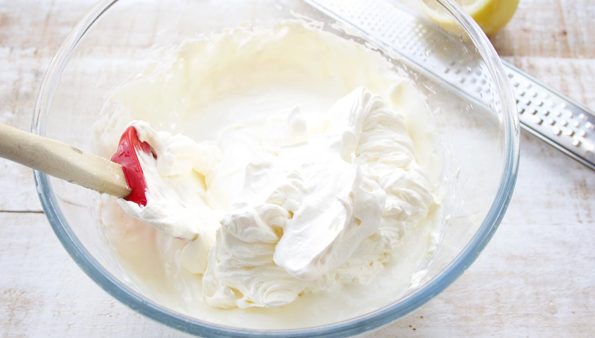 whipped cream and cream cheese mix and a spatula in a bowl