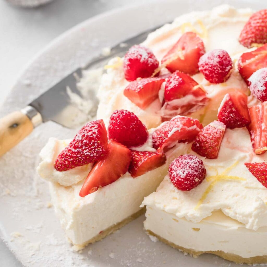 a no bake sugar free cheesecale topped with whipped cream, raspberries and strawberries