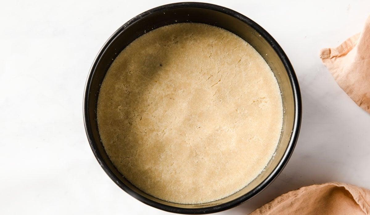 almond flour cake base in a springform tin