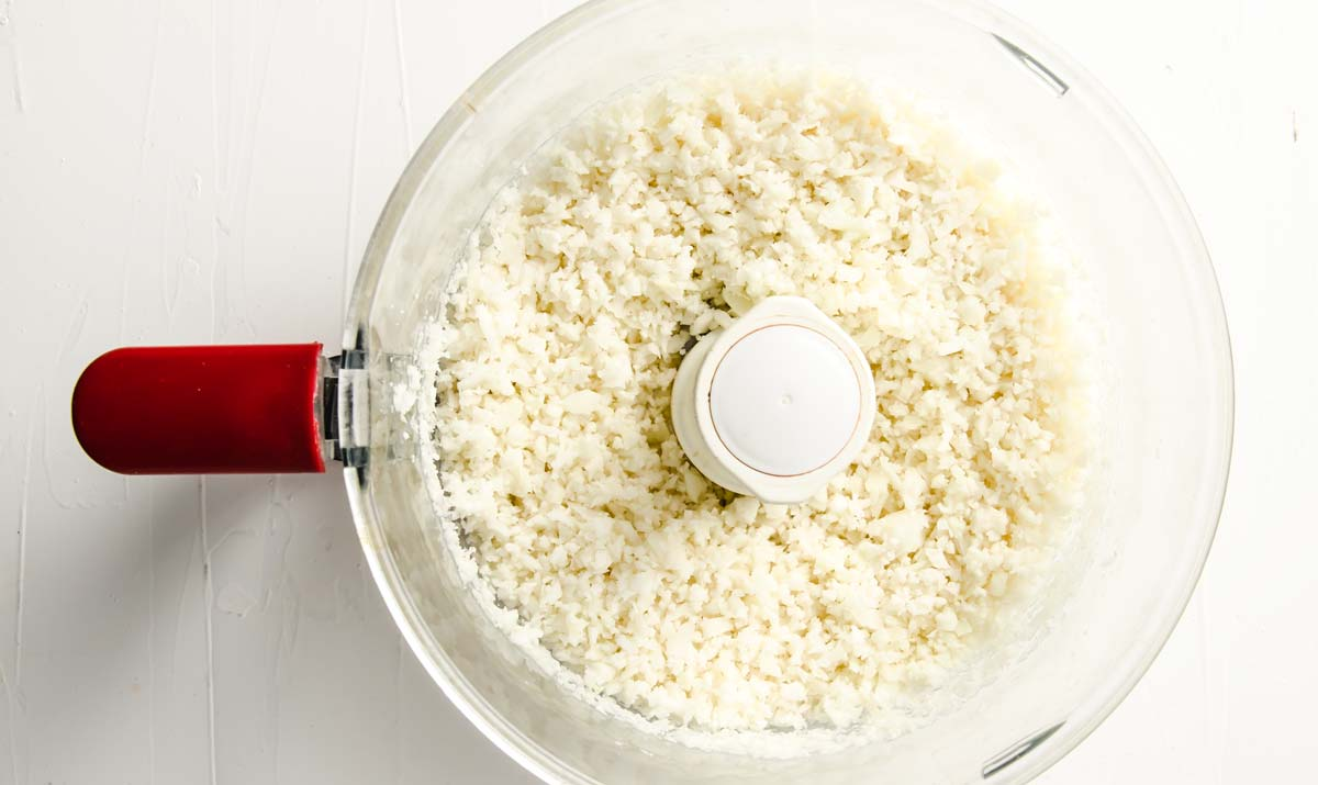 raw cauliflower rice in a food processor bowl