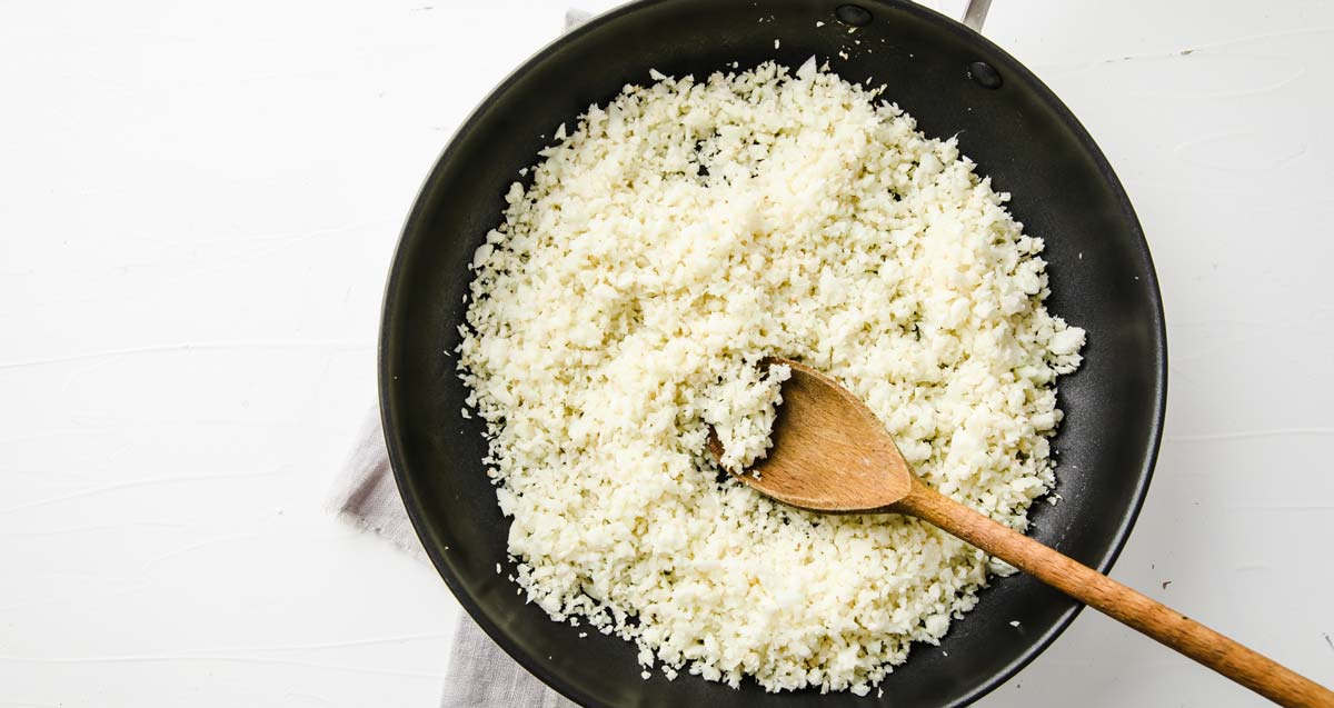 sauteeing cauliflower rice in a pan