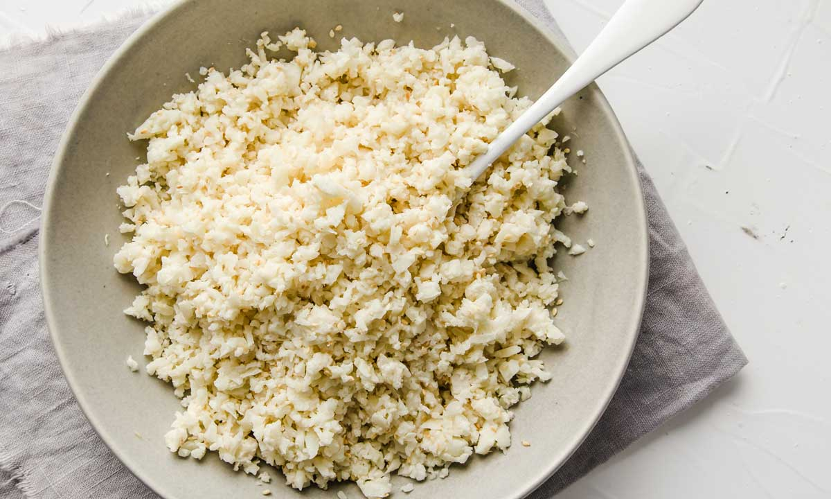 mixing the sesame seeds and cauliflower rice