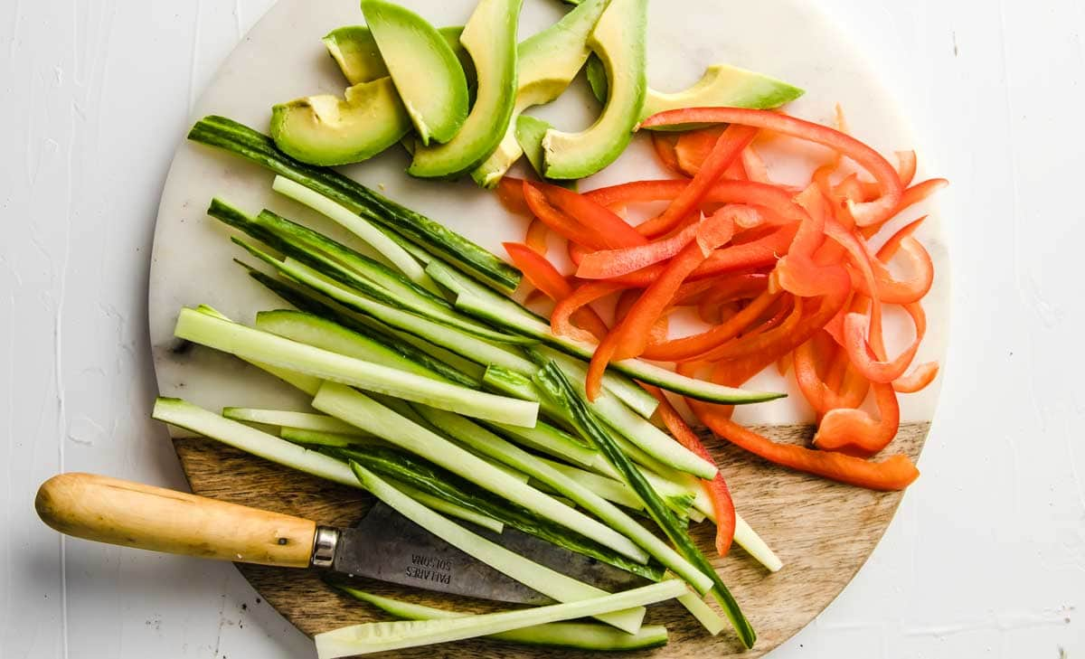 slicing avocado, peppers and cucumber with a knife
