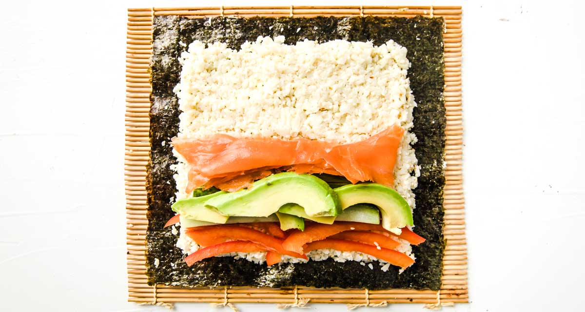 A nori square topped with cauliflower rice, avocado, cucumber, peppers and smoked salmon on a bamboo mat
