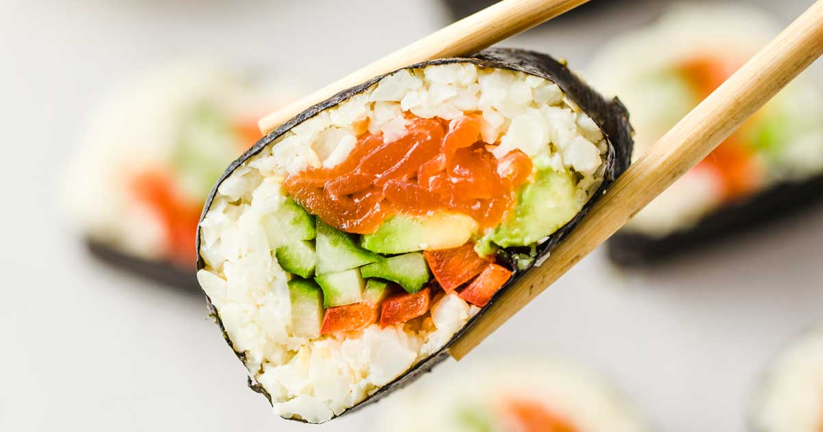 picking up a keto sushi roll with chopsticks