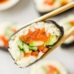 a pair of chopsticks lifting a low carb salmon sushi roll