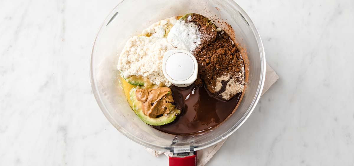avocado, chocolate and other ingredients in a food processor bowl