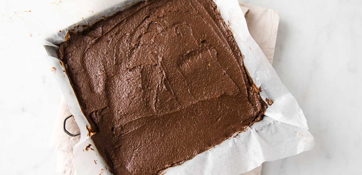 brownie batter in a square baking tin lined with parchment