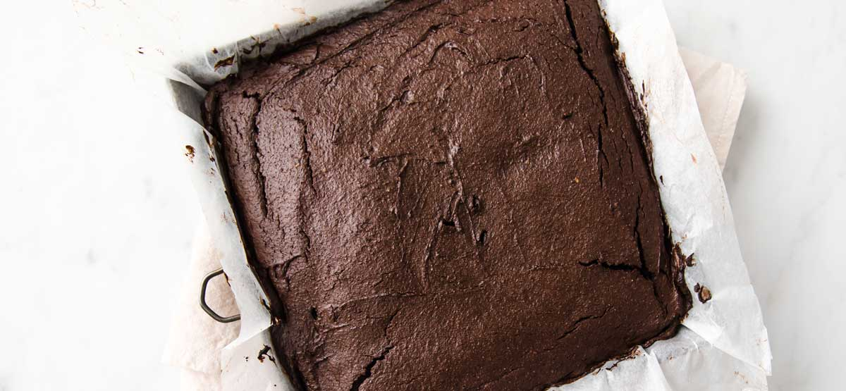 baked avocado brownie base in a square baking pan