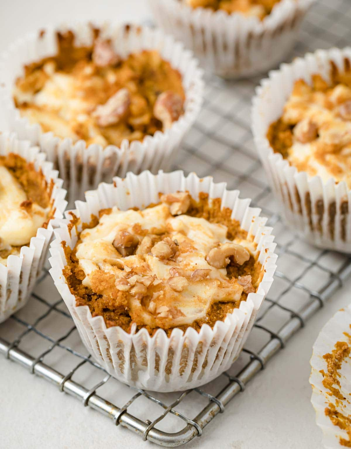 pumpkin cheesecake muffins in paper cases on a cooling rack