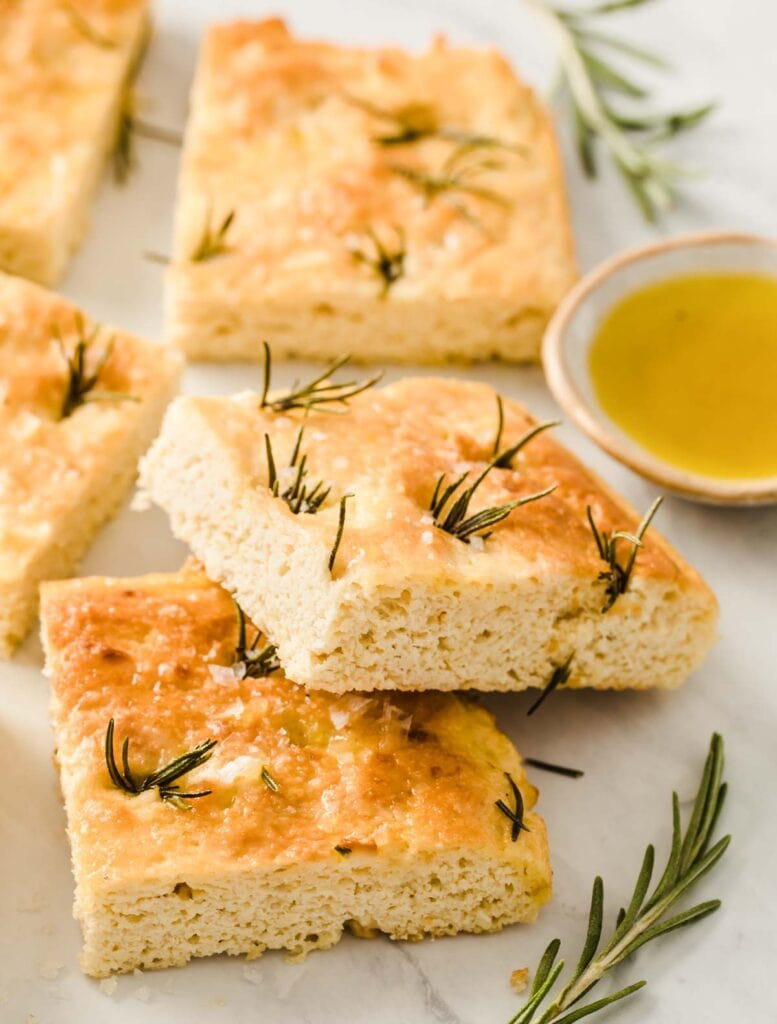 squares of focaccia bread with rosemary sprigs and a small dish of olive oil