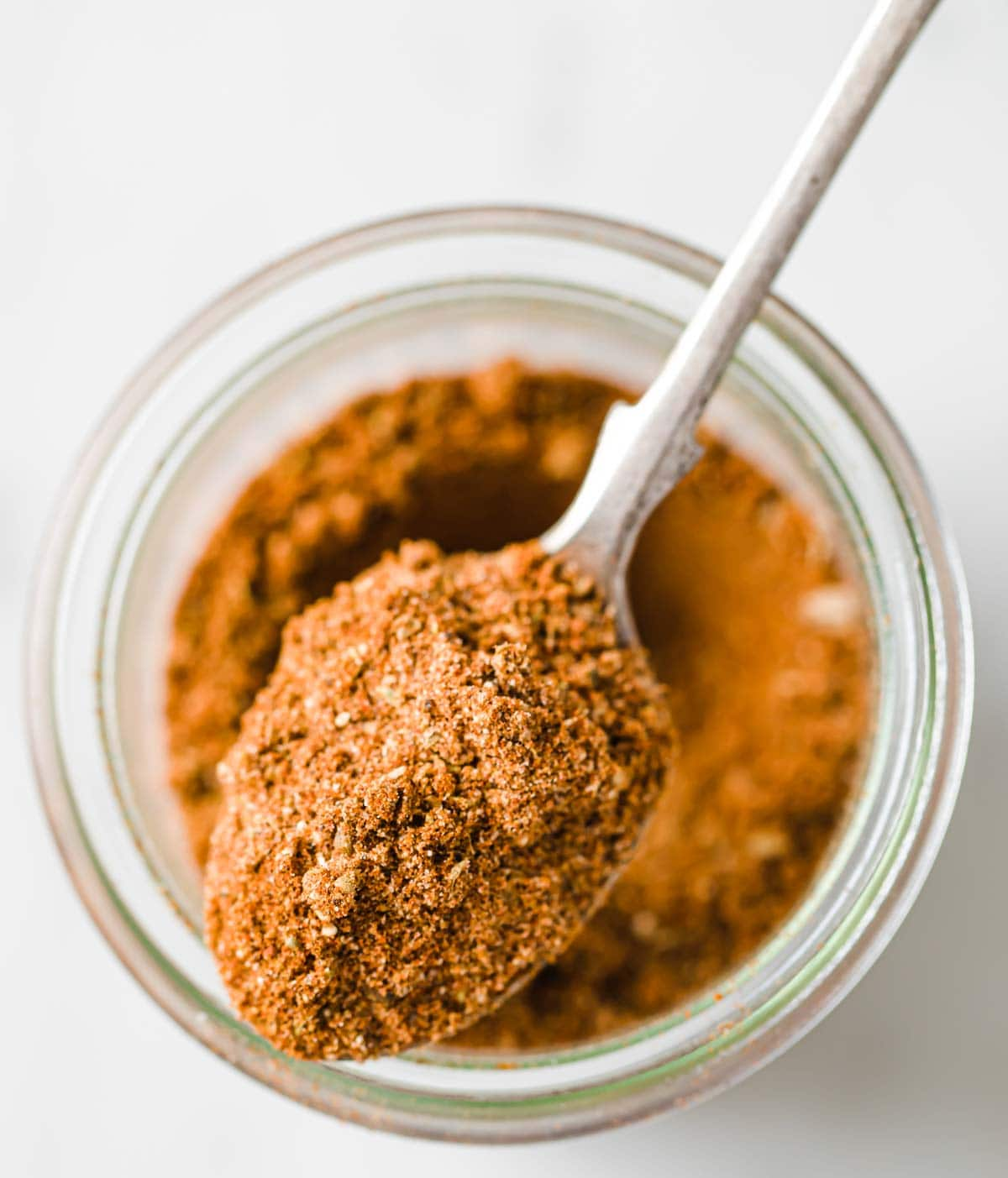 a spoon with homemade taco seasoning lying on top of a glass jar with seasoning