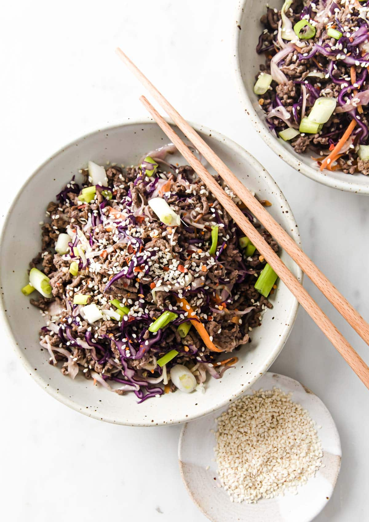 stir fried ground beef and cabbage aka crack slaw with spring onions and sesame seeds on a plate with chopsticks