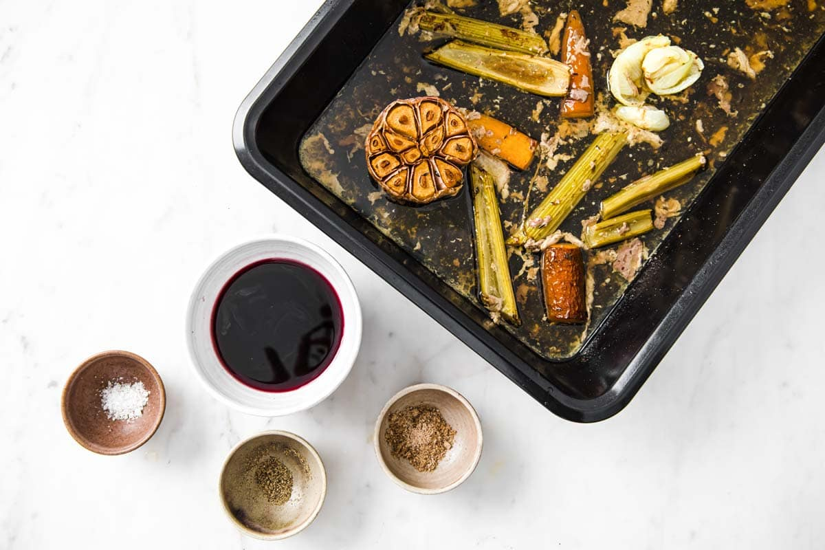 roasted vegetables and turkey pan juices in a pan and other ingredients in bowls