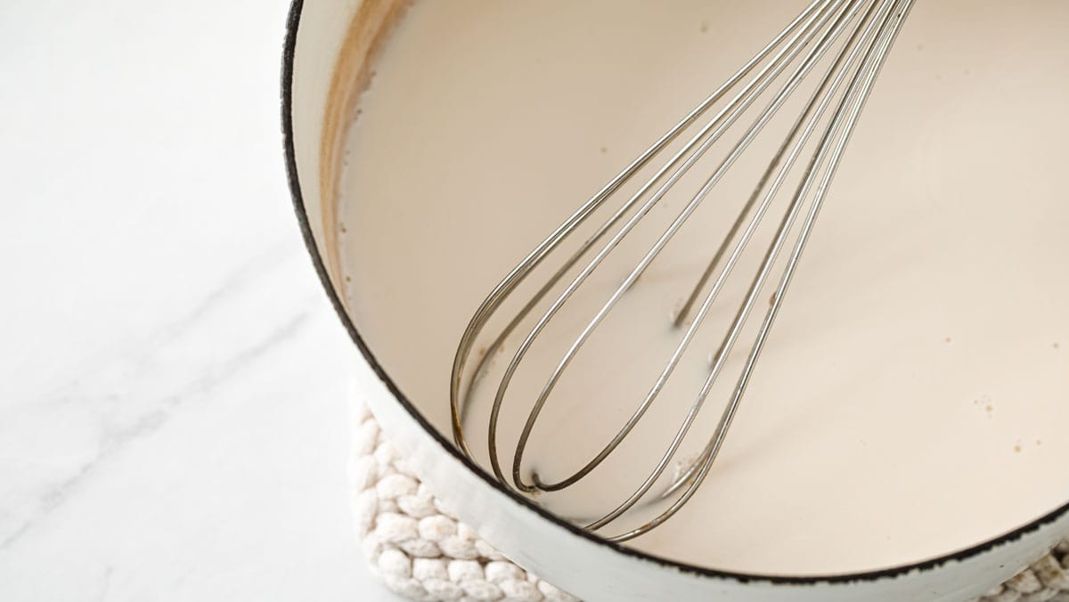 almond milk in a saucepan and a whisk