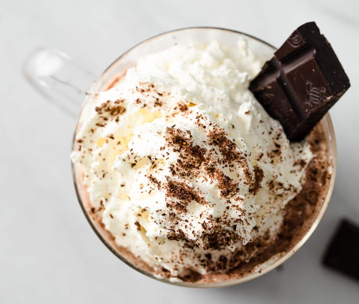 a square of dark chocolate in whipped cream decorating a hot chocolate