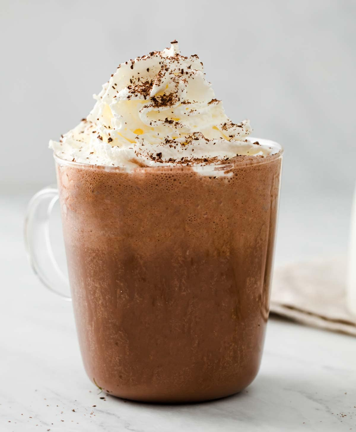 a glass cup filled with frothy hot chocolate topped with cream