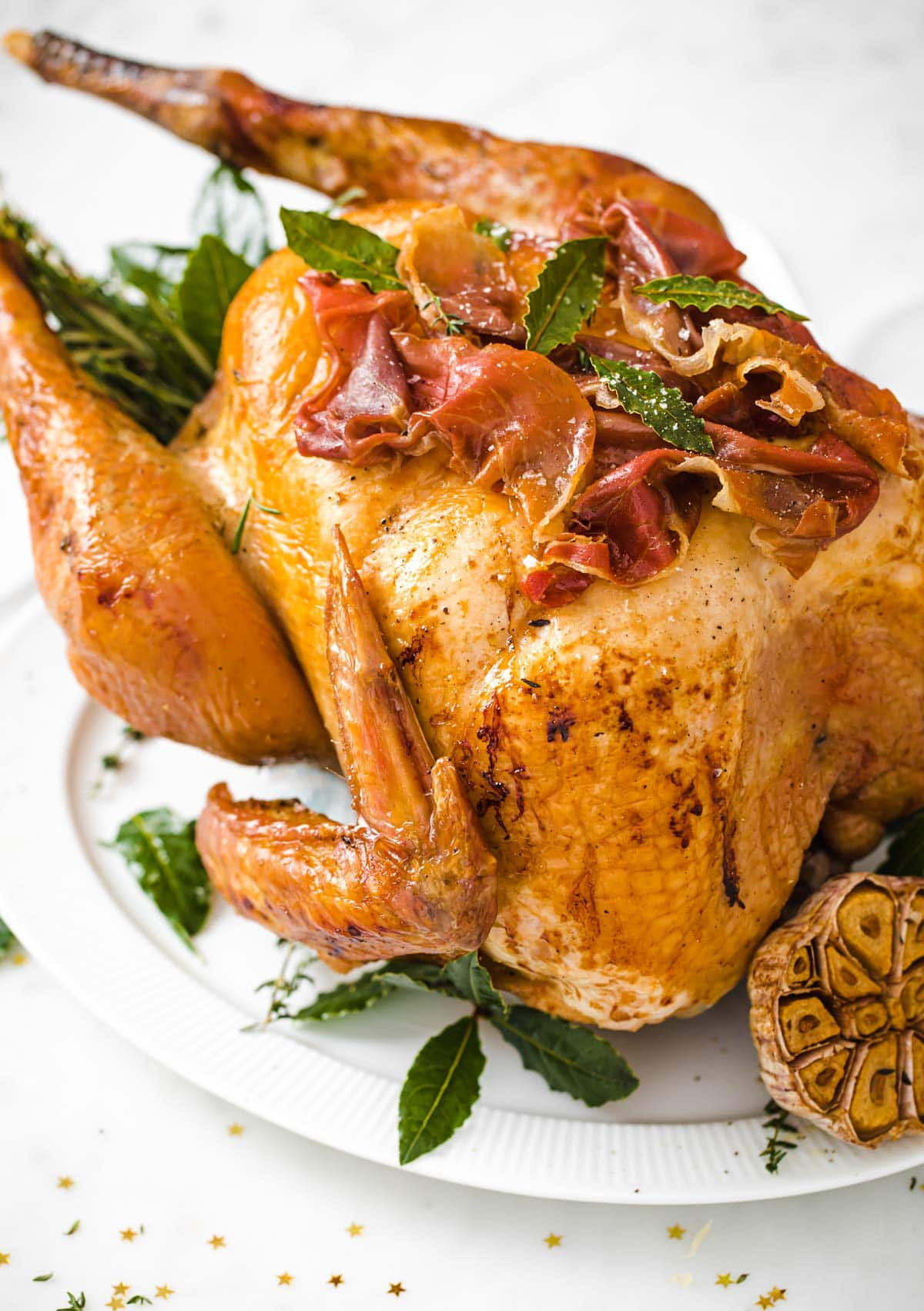 a roasted turkey stuffed with herbs and sage leaves