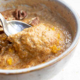 a bowl with pumpkin porridge and a spoon