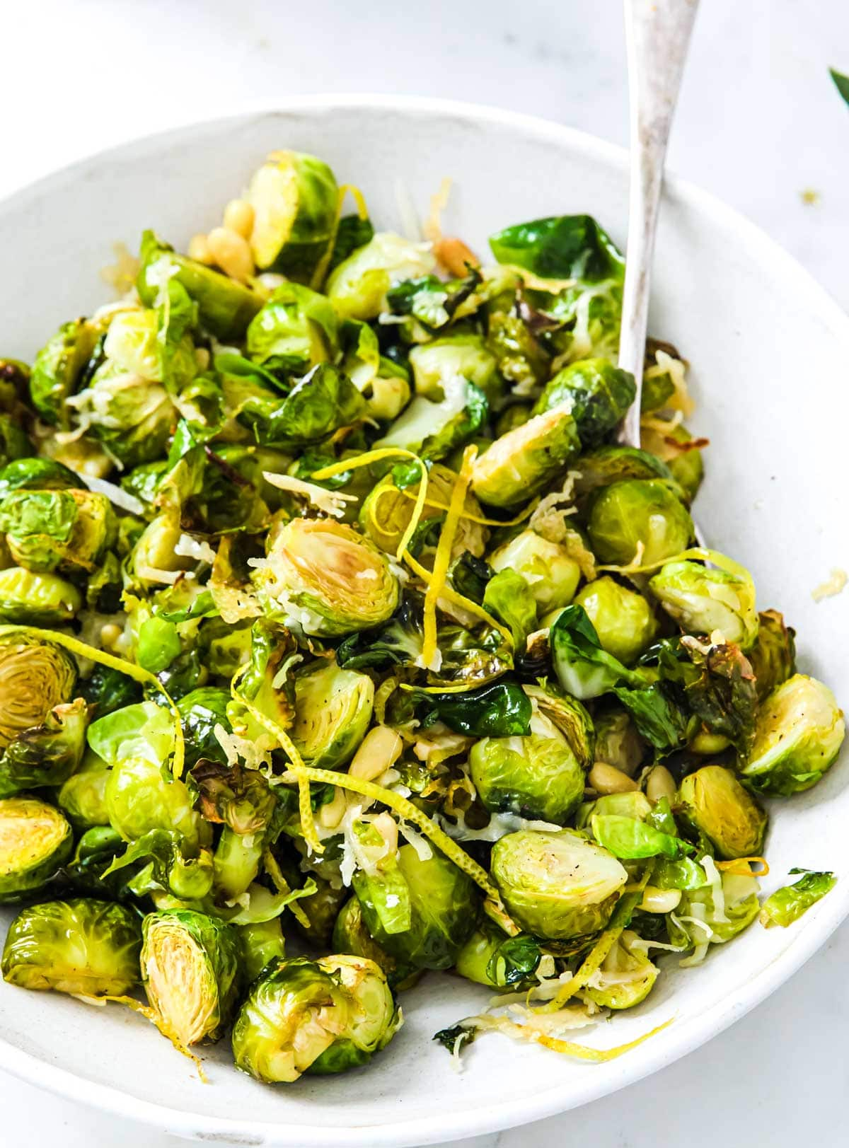 a serving bowl with roasted sprouts, parmesan and lemon zest and a spoon