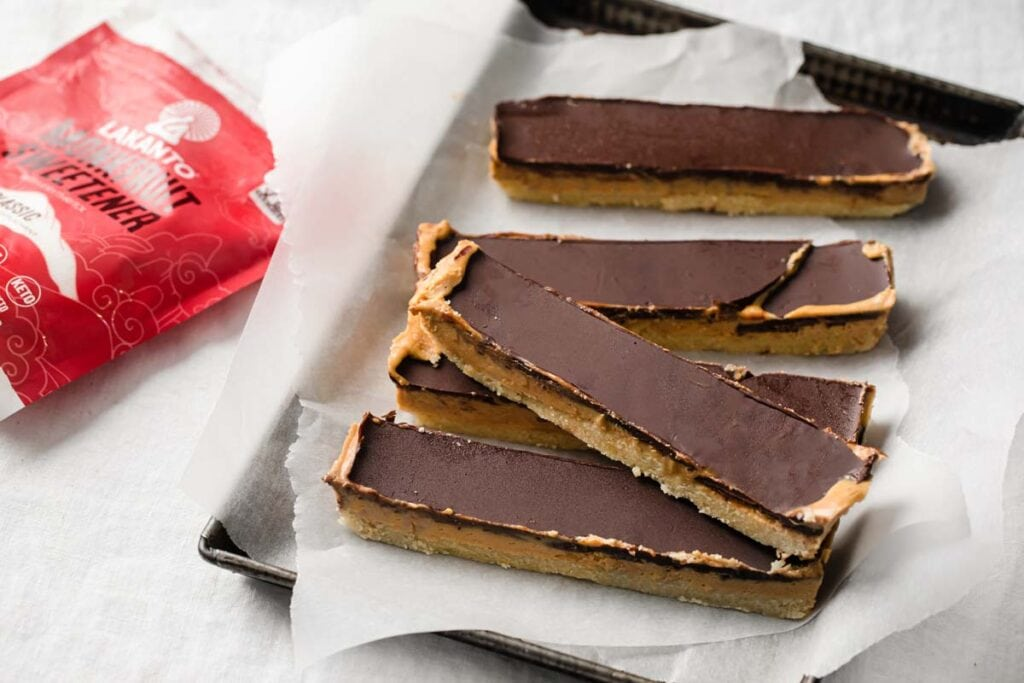 peanut butter slices with chocolate topping in a baking tray