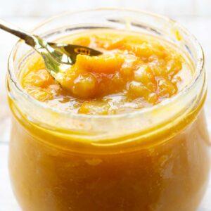 taking a spoonful of sugar free orange marmalade from a glass jar