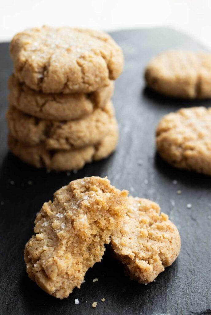 an almond flour peanut butter cookie broken in half showing the moist centre