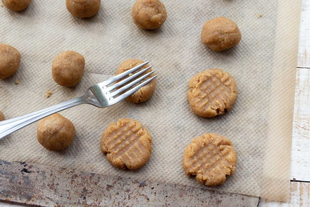 unbaked cookies on a baking sheet and a fork making criss cross patterns