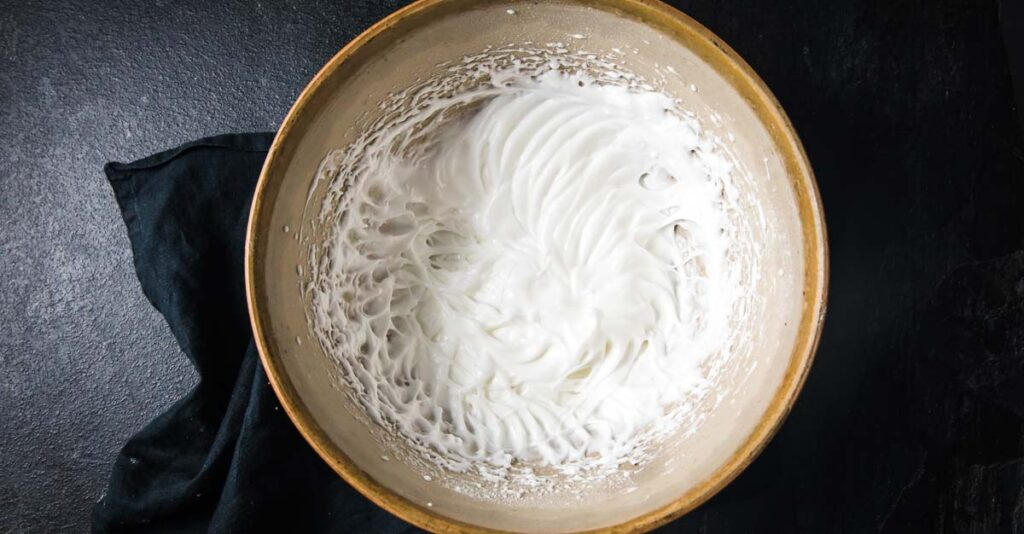 stiff egg whites in a bowl with sweetener