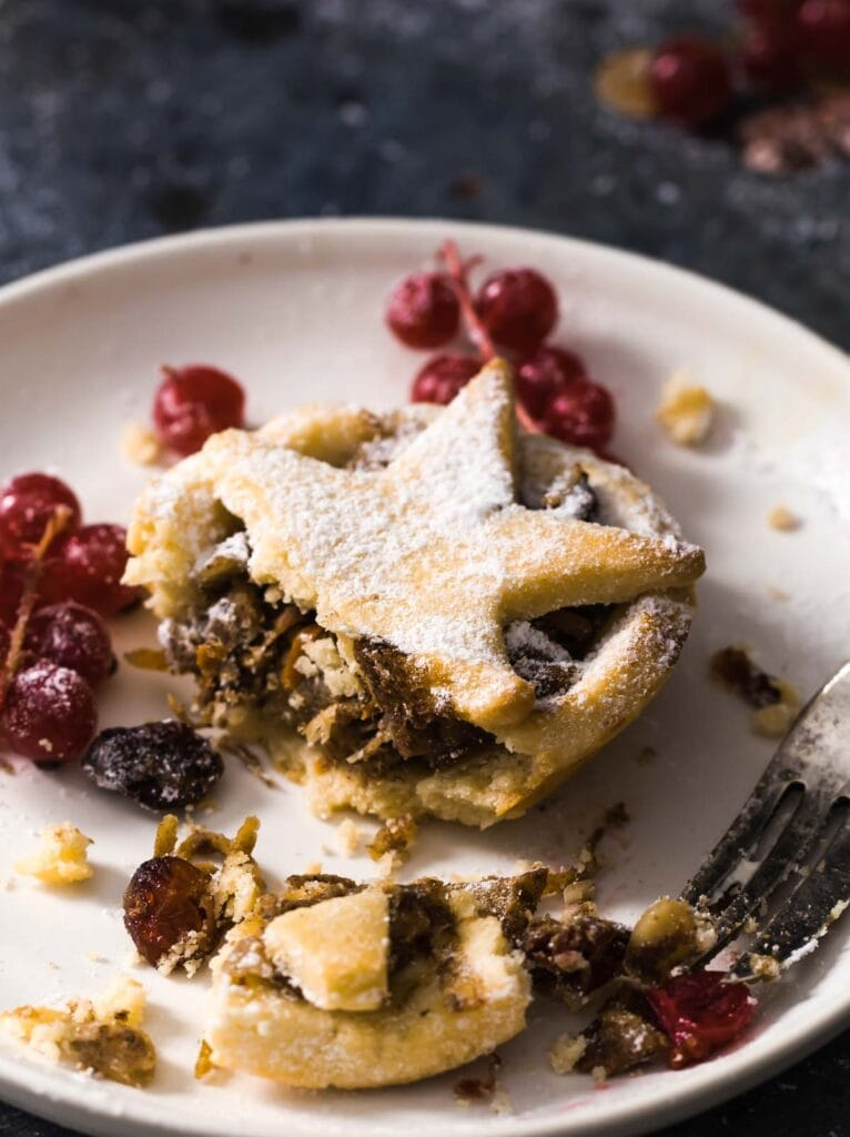 a mince pie on a plate with a bite taken out by a fork