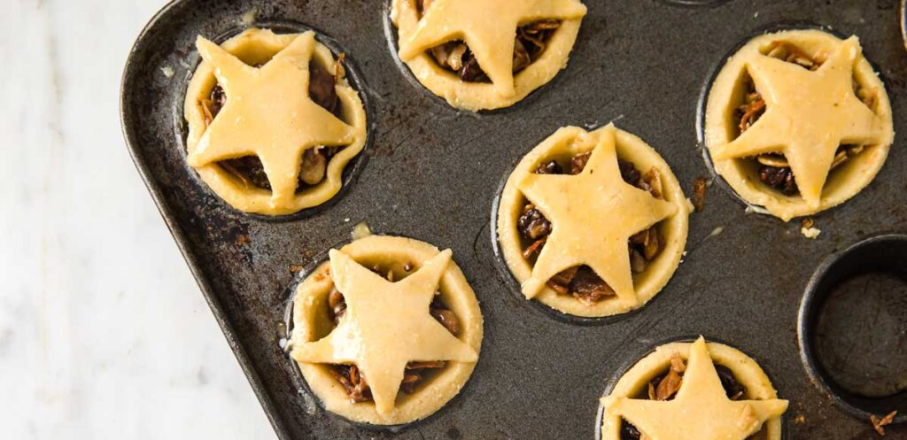 unbaked mince pies in a baking pan