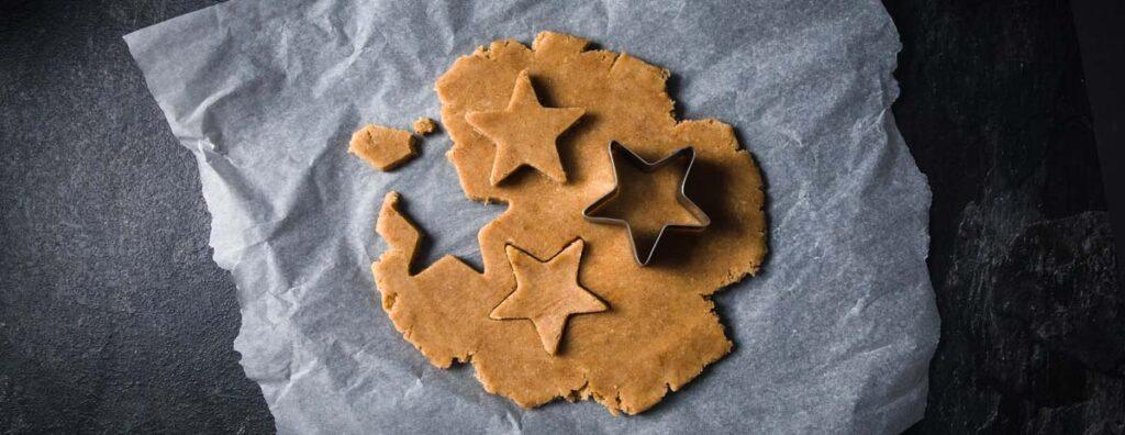 cookie dough on parchment paper with a star cookie cutter