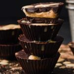a stack of 4 keto peanut butter cups, the top one is halved showing the peanut centre