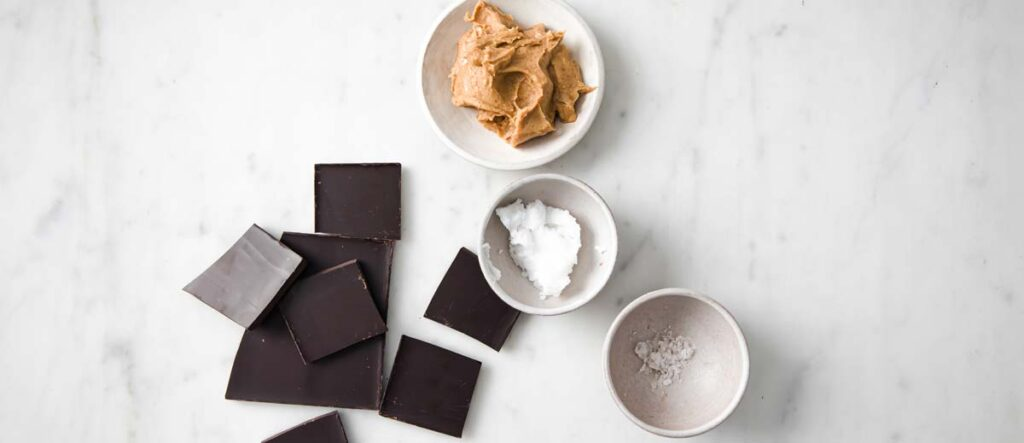 broken chocolate pieces, peanut butter, coconut oil and salt in bowls
