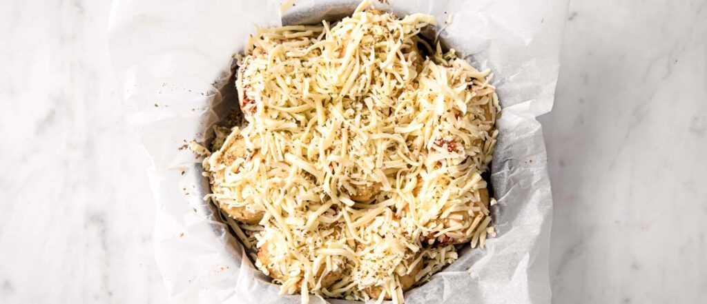 unbaked rolls in a pan lined with parchment paper topped with grated cheese