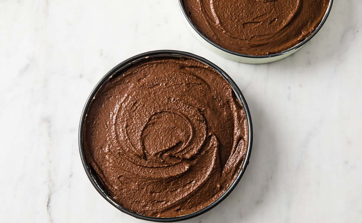 chocolate cake batter in two cake tins