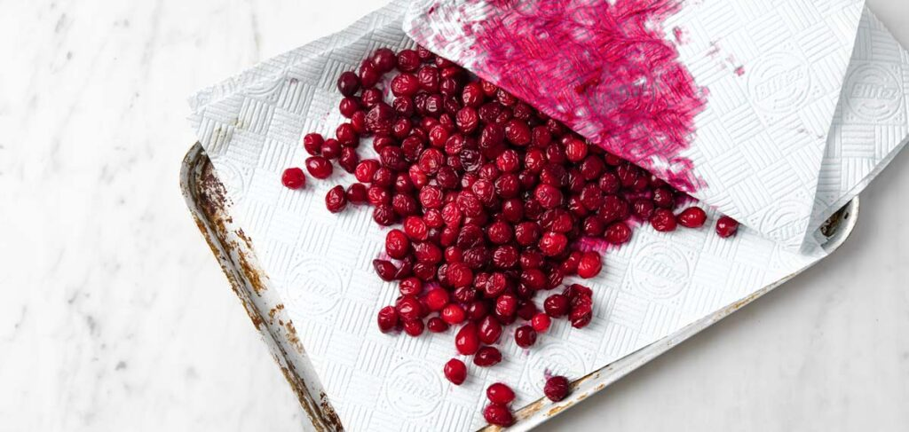 blotting juice and liquid off cranberries with a paper towel