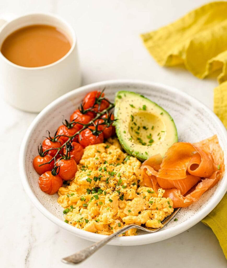 scrambled eggs with cherry tomatoes, avocado and salmon on a plate